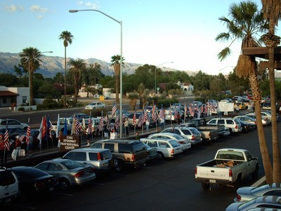 In front of the recruiting center, many people, signs, flags, traffic